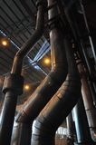 Power Pipes. Steel roof structure and metal silver pipe in the complex process of generating electricity at in a coal burning electricity generating plant. Early Royalty Free Stock Photography