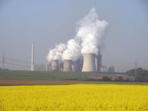 Power Plant. Power station with smoking cooling towers behind a canola field Royalty Free Stock Photo