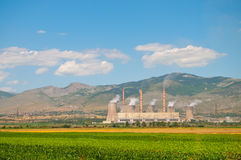 Power Plant. With smoking chimneys and green field in Greece Royalty Free Stock Photo