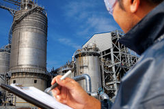 Power plant. Engineer oil refinery write on the notes book looking large oil refinery focus on refinery buiding Royalty Free Stock Images