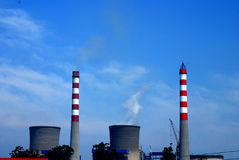Power Plant. High in the blue sky under the power plant chimney Royalty Free Stock Image