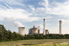 Power Plant Behind Field And Trees. A large coal-fired power station behind some trees and a field Stock Image