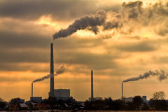 Power plant with burning yellow sky behind Stock Photos