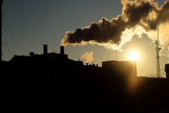 Power plant chimney smoking at sunset backlit toned image Stock Images