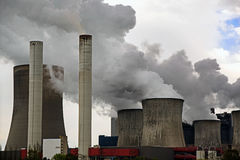 Power plant with chimneys and steaming cooling towers, gray clou Royalty Free Stock Images