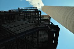Power Plant 3. Concrete smoke stack with emissions visible. Steel stairs going up several levels at the outside of the plant building Royalty Free Stock Images