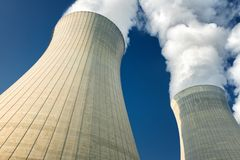 Power plant cooling towers steaming. On dark blue sky background stock photography