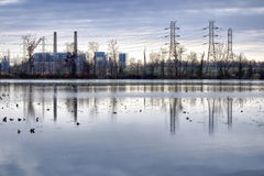 Power Plant and Electric Transmission Power Lines. Coal fired electric energy generation plant with high voltage power transmission lines over wetland pond water Royalty Free Stock Images