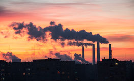 Power Plant emissions during sunrise in a city. Power Plant emissions seen above residential blocks from a city during sunrise. Environmental pollution. Factory stock photography