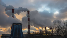 Power plant emitting smoke and vapor. In cold weather Stock Photos
