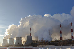Power plant emitting smoke and vapor. In cold weather Royalty Free Stock Photos