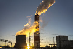 Power plant emitting smoke and vapor. In cold weather Stock Photography