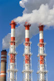 Power plant fumes. Vapors out in blue sky royalty free stock photography