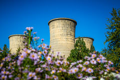 Power plant furnaces. With flowers in the foreground Stock Image
