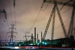 Power plant and high tension poles. Power plant, urban periphery High tension poles, transformation point; night scene, industrial site, metallic structures stock images