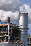 Power Plant II. Vertical image of a power plant closeup with stack emitting steam Royalty Free Stock Photos