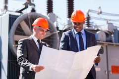 Power plant managers holding blueprint Royalty Free Stock Image