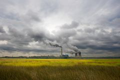 Power Plant Marsh. Power plant set on a colorful marsh with smoke and steam rising from cooling towers into a dark threatening sky Stock Photo