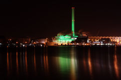 Power plant at night. A power plant illuminated with green and red lights at night. The lights are reflected by the waterfront royalty free stock images
