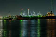 Power plant with shipping boat at night time. Industry for energy and shipping concept Stock Images