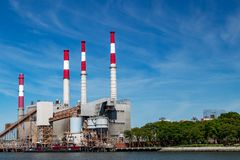Power plant smoke stack towers contrast against blue sky Stock Image