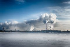 Power plant smokes in blue dramatic sky in a winter city. Free copyspace text Royalty Free Stock Photo