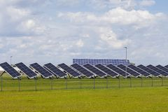 Power plant solar panels on a green field under a blue sky with fluffy clouds stock image