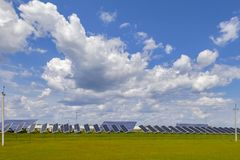 Power plant solar panels on a green field under a blue sky with fluffy clouds royalty free stock image