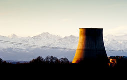 Power plant at sunset. Power plant cooling tower against snowy mountains at sunset. Picture taken in Trino, Italy Royalty Free Stock Photography