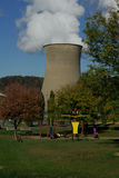 Power Plant and Swing. Large coal power plant with white smoke over looking Swing-set Stock Image