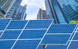 Power plant using renewable solar energy with city building back Stock Photo