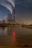 Power plant on water front by night with smoke in the chimneys Stock Photo