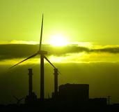 Power plant and wind turbines backlit at sunrise Royalty Free Stock Image