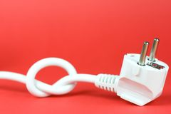 Power plug. Plug tied in a knot on red background Royalty Free Stock Photography