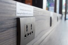 Power plug for charging mobile phone in a coffee shop in Thailand Royalty Free Stock Images