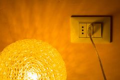 Power plug by a lighted lamp. Power plug by a lighted table lamp stock image
