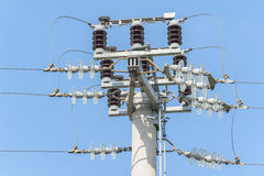 Power pole with external electric separator on top. Power isolator switch manual on electrical pylon against the blue sky Stock Images