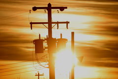 Power pole in silhouette. A power pole is silhouetted by the rising sun stock images