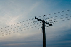 Power pole silhouetted at dusk Royalty Free Stock Photos