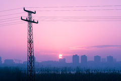 Power pole silhouettes in red purple cloudy sunset Royalty Free Stock Image