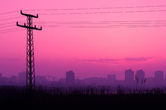 Power pole silhouettes in red purple cloudy sunset Royalty Free Stock Photo