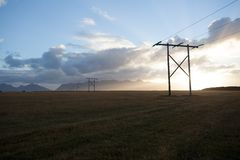 Power pole with sunset in Iceland. Light and shadow over the lan. Dscape. Beautiful mountain range in the backgrond. Tough nature Royalty Free Stock Photo