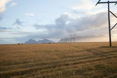 Power pole with sunset in Iceland. Light and shadow over the lan. Dscape. Beautiful mountain range in the backgrond. Tough nature Royalty Free Stock Photos