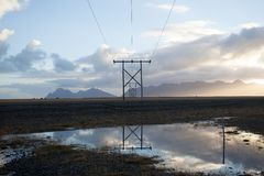 Power pole with sunset in Iceland. Light and shadow over the lan. Dscape. Beautiful mountain range in the backgrond. Tough nature Stock Photography