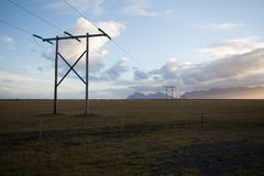 Power pole with sunset in Iceland. Light and shadow over the lan. Dscape. Beautiful mountain range in the backgrond. Tough nature Stock Photos