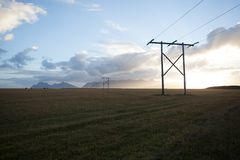 Power pole with sunset in Iceland. Light and shadow over the lan. Dscape. Beautiful mountain range in the backgrond. Tough nature Royalty Free Stock Image