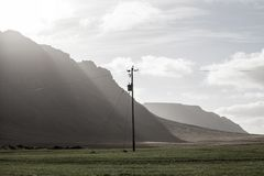 Power pole with sunset in Iceland. Light and shadow over the lan. Dscape. Beautiful mountain range in the backgrond. Tough nature Stock Image