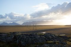 Power pole with sunset in Iceland. Light and shadow over the lan. Dscape. Beautiful mountain range in the backgrond. Tough nature Stock Images