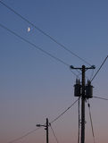 Power poles and the moon. Power poles and the half moon royalty free stock image