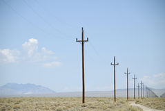 Power poles receding to infinity. A row of desert telegraph poles recede into the hazy horizon Stock Photography